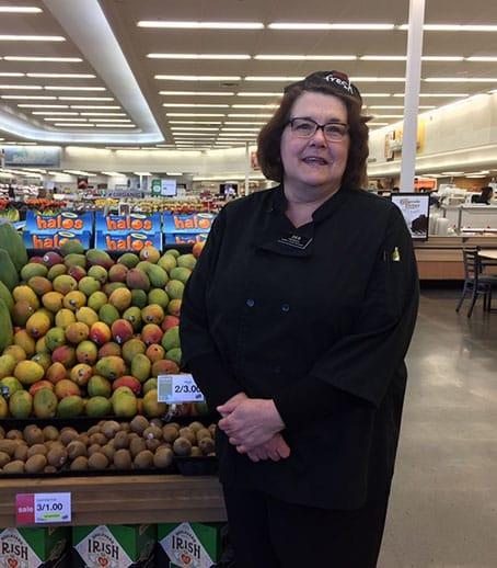 Debbie Standing in Front of Mango Produce