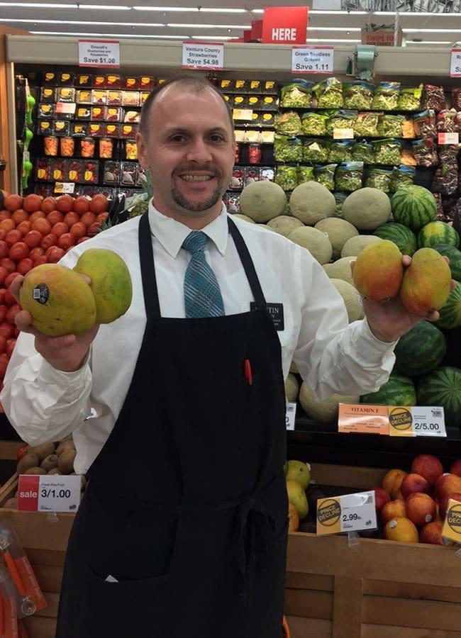 Produce Manager Holding Mangos