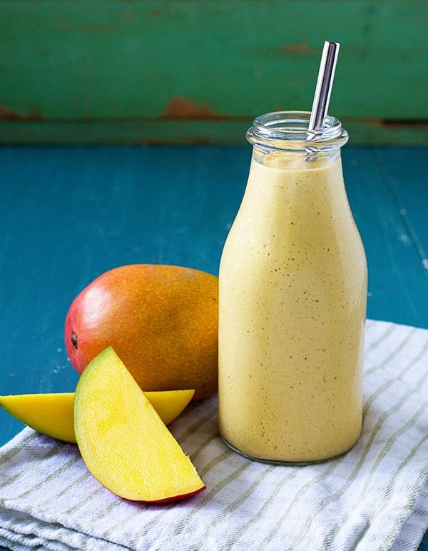 Mango Smoothie in Jar next to Mangos
